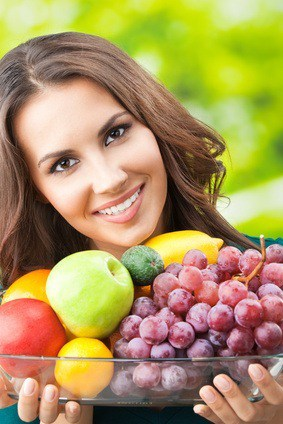 Girl holding healthy fruit and vegetables for good diet composition